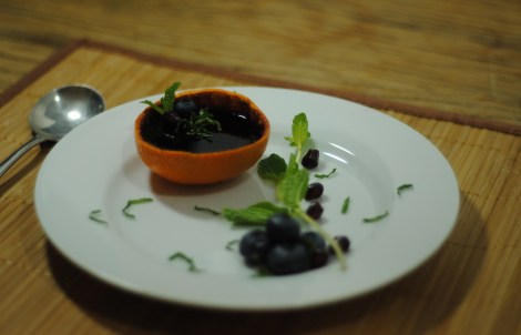 Blueberry vanilla jello dessert with mint chiffonade, served in an orange rind (photo)